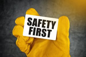 38645450 - safety first on business card, male hand in yellow leather construction working protective gloves holding card with rounded corners.