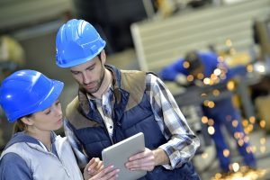 Male and female safety professional discussing something about the workplace using a tablet